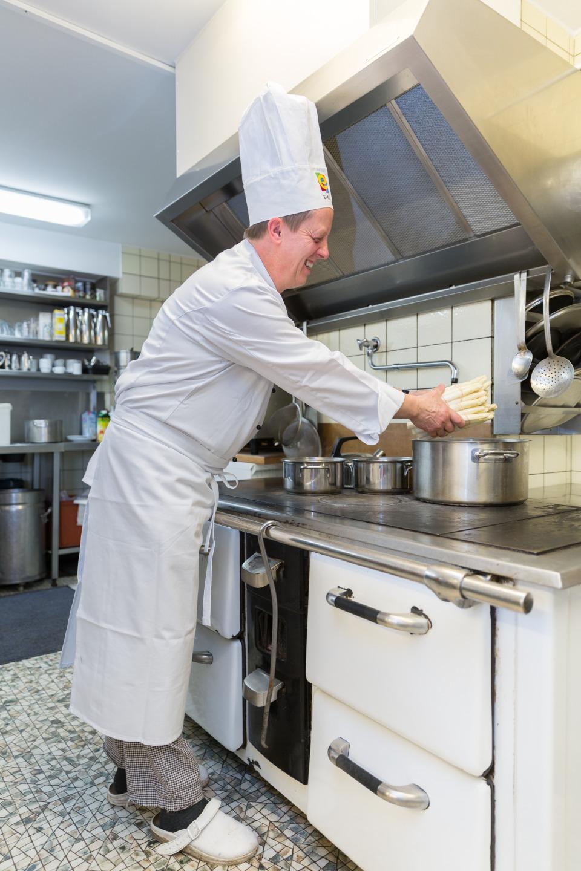 Der Küchenchef am Holzkohleherd mit Spargel