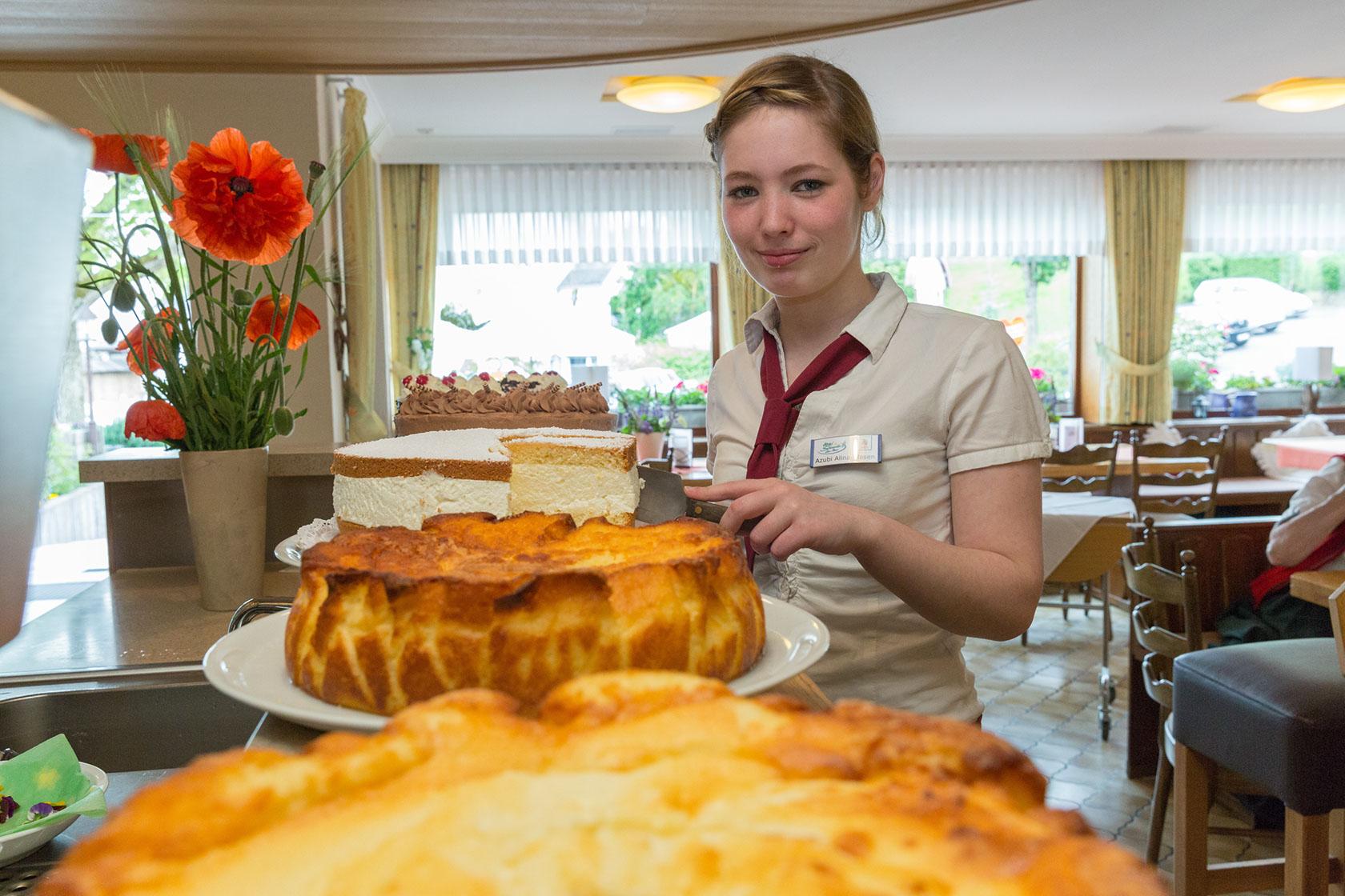Kellnerin beim Kuchen schneiden