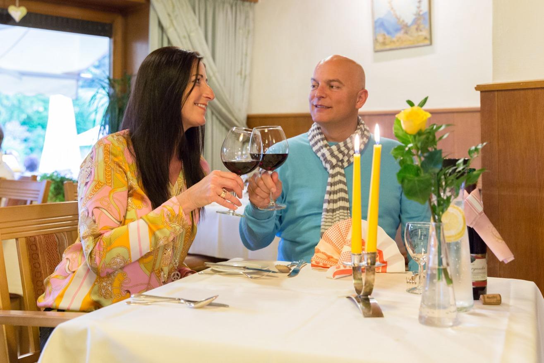 Paar stößt mit einem Rotwein auf einen schönen Abend an